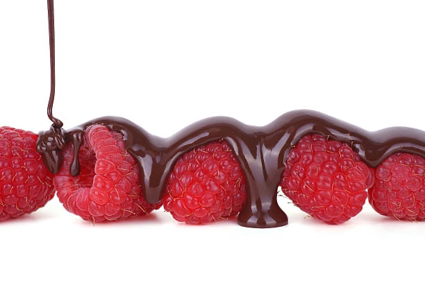 Dark melted chocolate pours over a row of ripe raspberries.