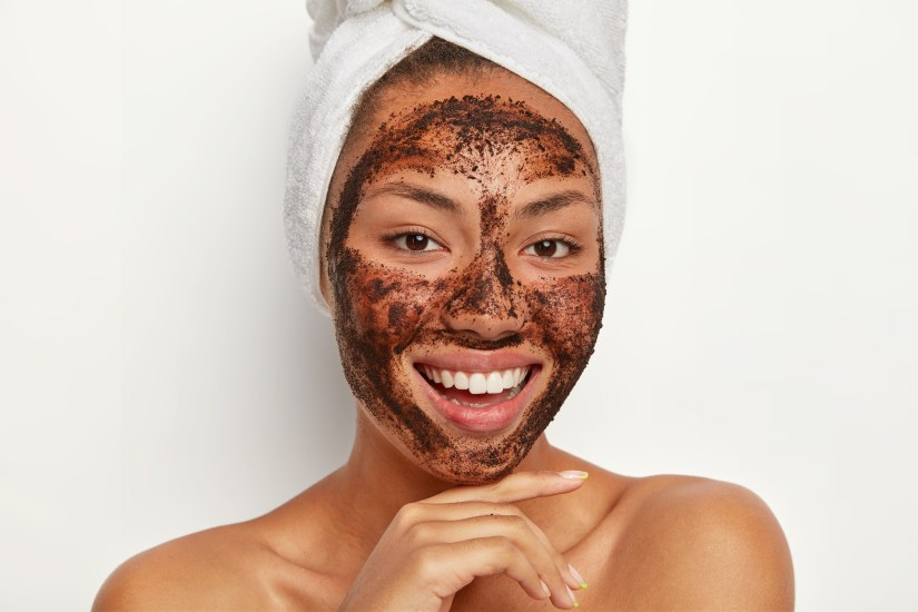 Beautiful girl with coffee face mask and beautiful smile