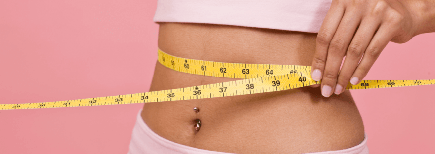 Girl measuring her weight loss with pcos