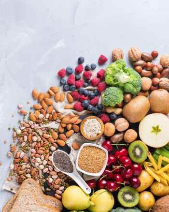 A variety of vegan foods on a counter clustered together including fruit, vegetables, beans, nuts, seeds, and bread.