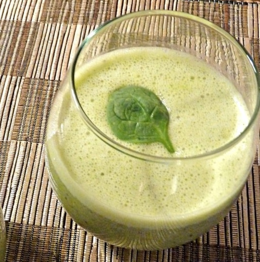 A glass of green tea smoothie topped with a spinach leaf