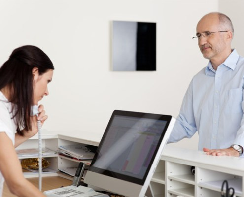 Man talking to doctor's receptionist