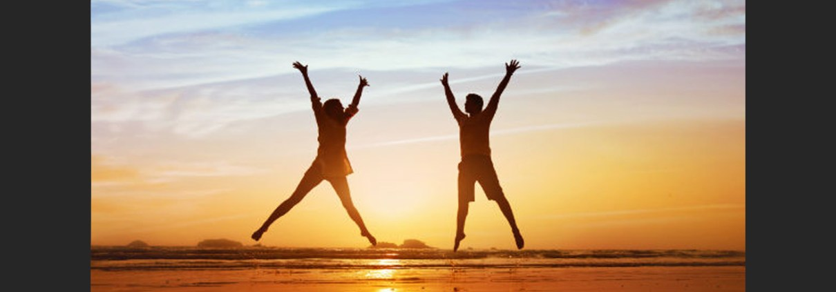 Silhouettes of two people jumping on a beach