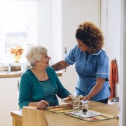 Care worker making a meal for elderly lady
