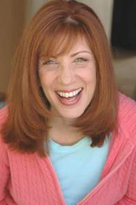 Photo of Nina Giovannitti smiling with bangs and shoulder length red hair, wearing a pink salmon cardigan and light blue shirt.