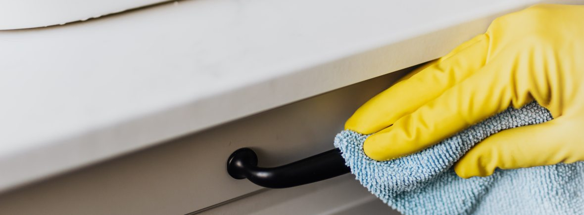 Yellow gloved hand wipes a black drawer handle on a white bathroom sink console with a blue washcloth.