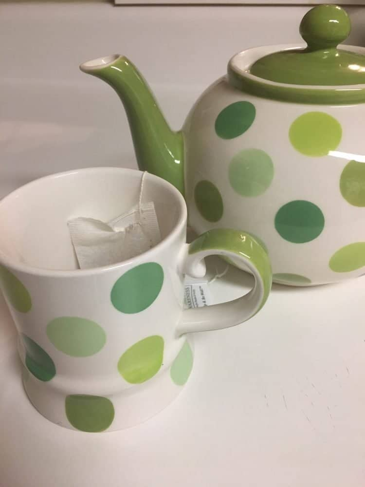 Green and white polka dot teapot and teacup - tea is great if you're wondering how to cure a cold.
