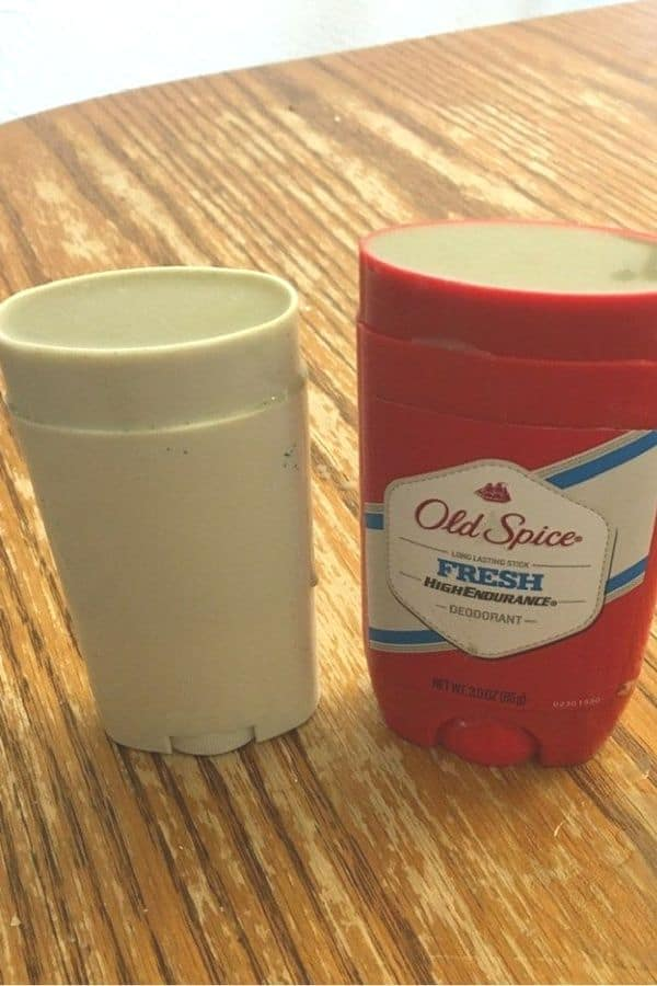 Two Homemade DIY Deodorant in stick deodorant canisters on a wood surface.