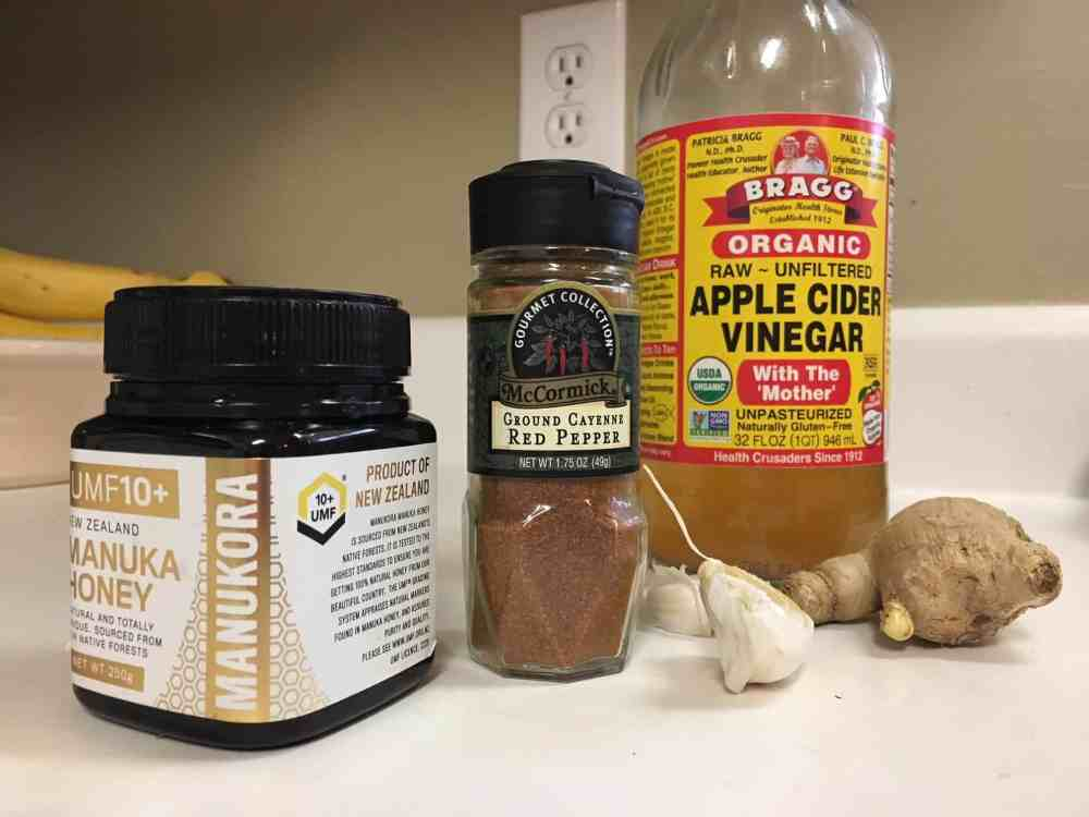 Ingredients for how to cure a cold with super tonic: manuka honey, cayenne pepper, apple cider vinegar bottles with ginger and garlic on a kitchen countertop.