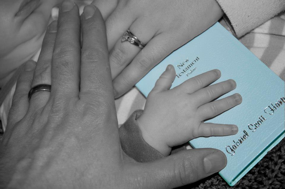 Bible verses about mothers - a mother, father, and baby's hands all on top of a bible.