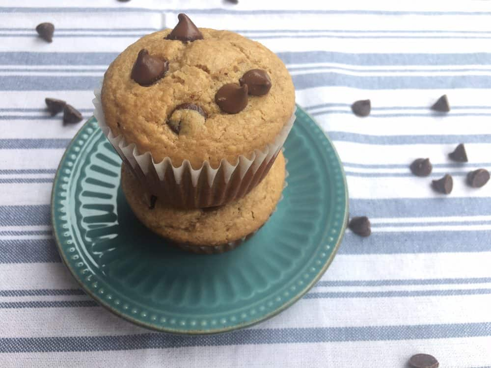 Peanut butter chocolate chip muffins, stacked on a small blue decorative plate with chocolate chips scattered around.