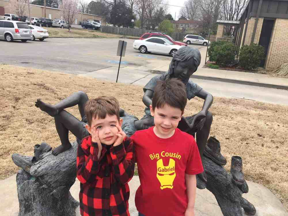 Two boys in front of a statue at the public library.