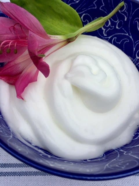 Homemade lotion in a blue pottery bowl with a pink flower on top.