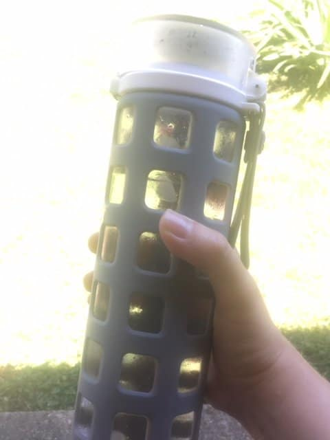 Person holding a water bottle outside.