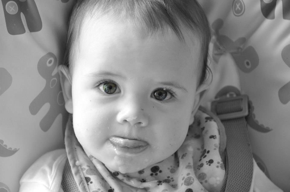 Black and white photo of a baby in a highchair licking his lips.