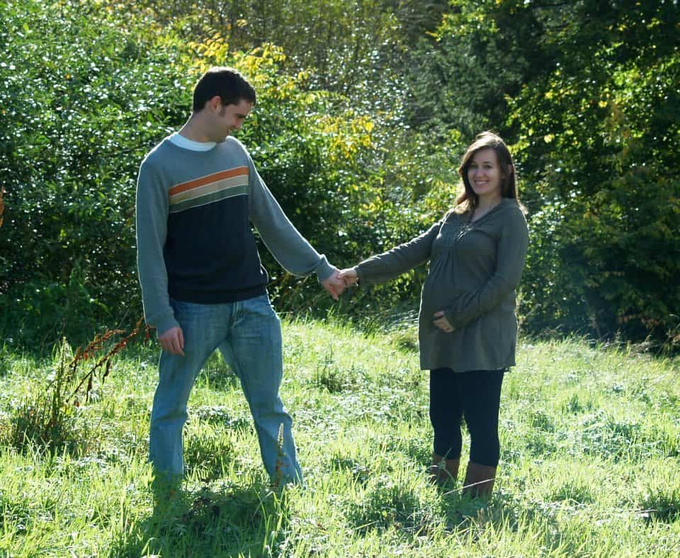 Maternity photo of man and woman holding hands in a meadow.