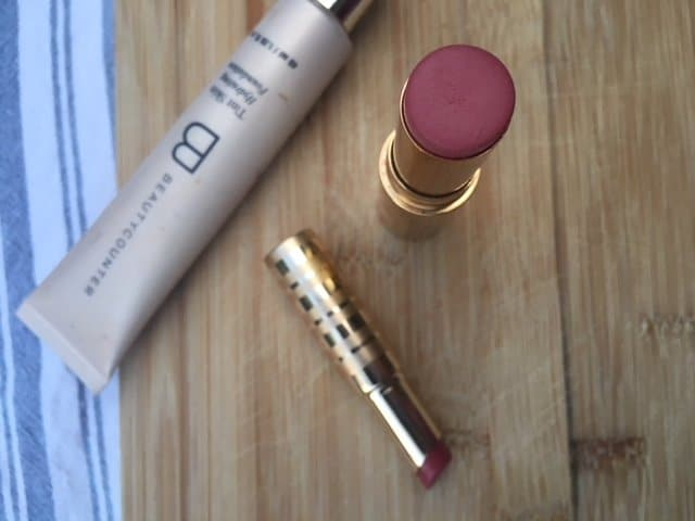 Natural makeup scattered across a wooden surface, including lipstick and gloss.