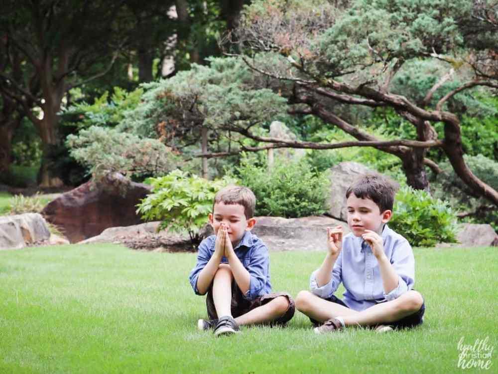 Children saying kids prayers outside.