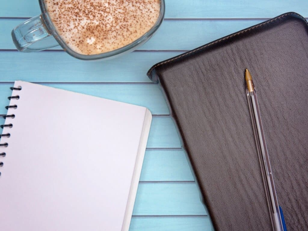 Prayer journaling notebook, pen, bible, and cappuccino sitting on a blue wooden table.