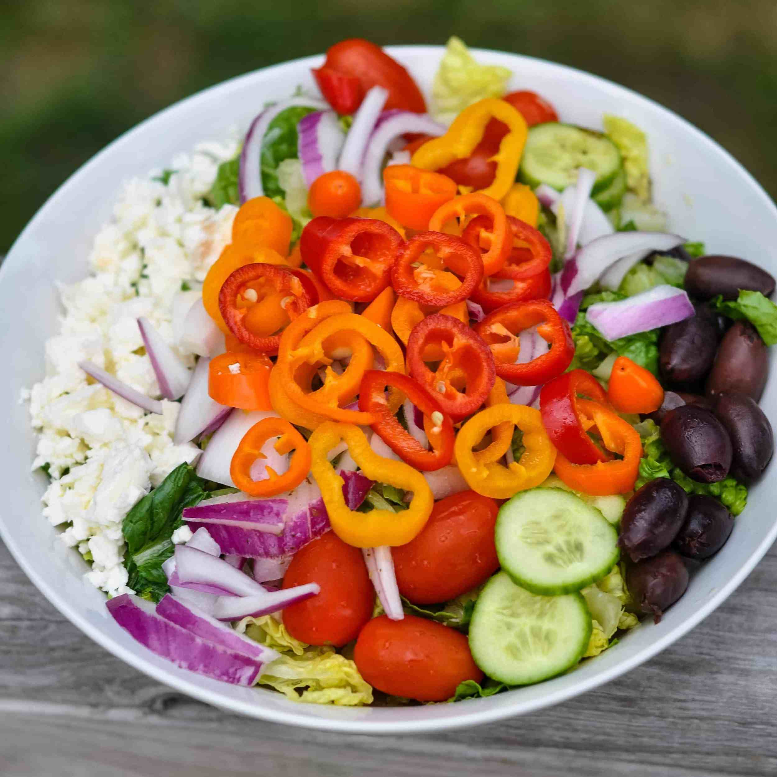 Greek salad in a large bowl topped with mini sweet peppers.