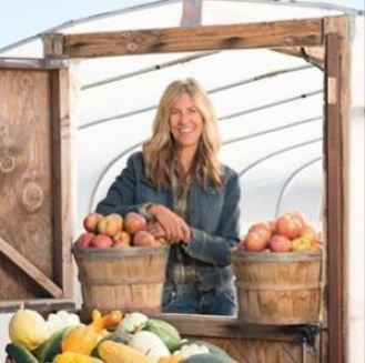 Wendy Madson standing next to baskets of fruit.