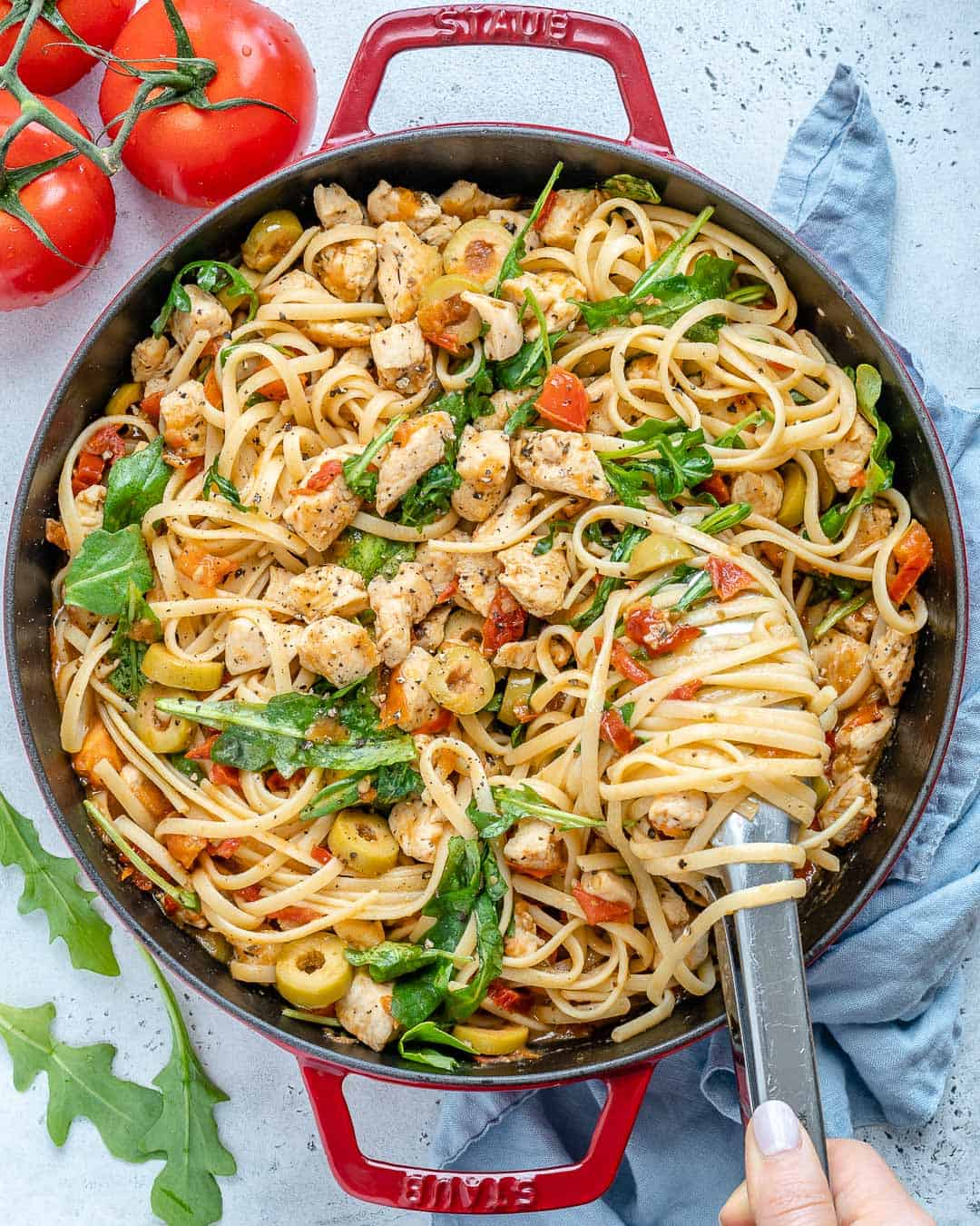 chicken spaghetti in a red skillet which utensil grabbing some pasta.