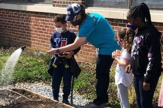 Program Manager, Lindsay Lancaster, helps 3rd grade students at Highlands Elementary School hand water the garden.