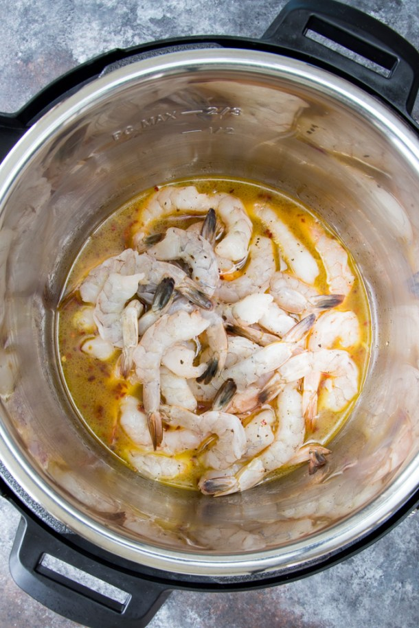 Process photo showing raw shrimp placed into the Instant Pot with melted butter and garlic just prior to cooking