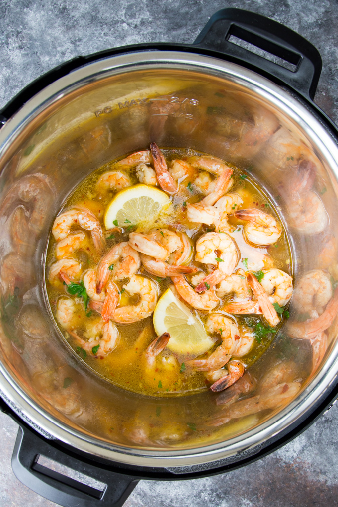 Instant Pot Shrimp Scampi - process photo showing cooked shrimp in melted butter and garlic in the Instant Pot with fresh parsley and lemon