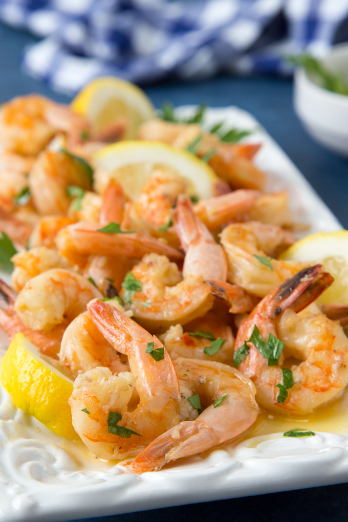 Instant Pot Shrimp Scampi (Keto, Low Carb & Gluten Free)- up close photo of cooked shrimp scampi with fresh lemon and parsley on a white platter
