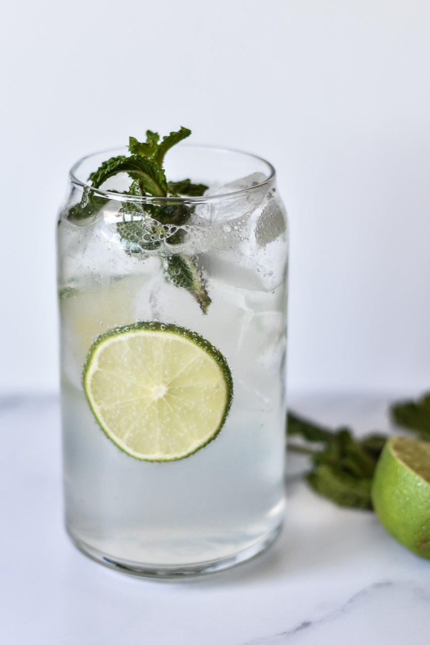 mojito mocktail in a tall glass with limes and mint