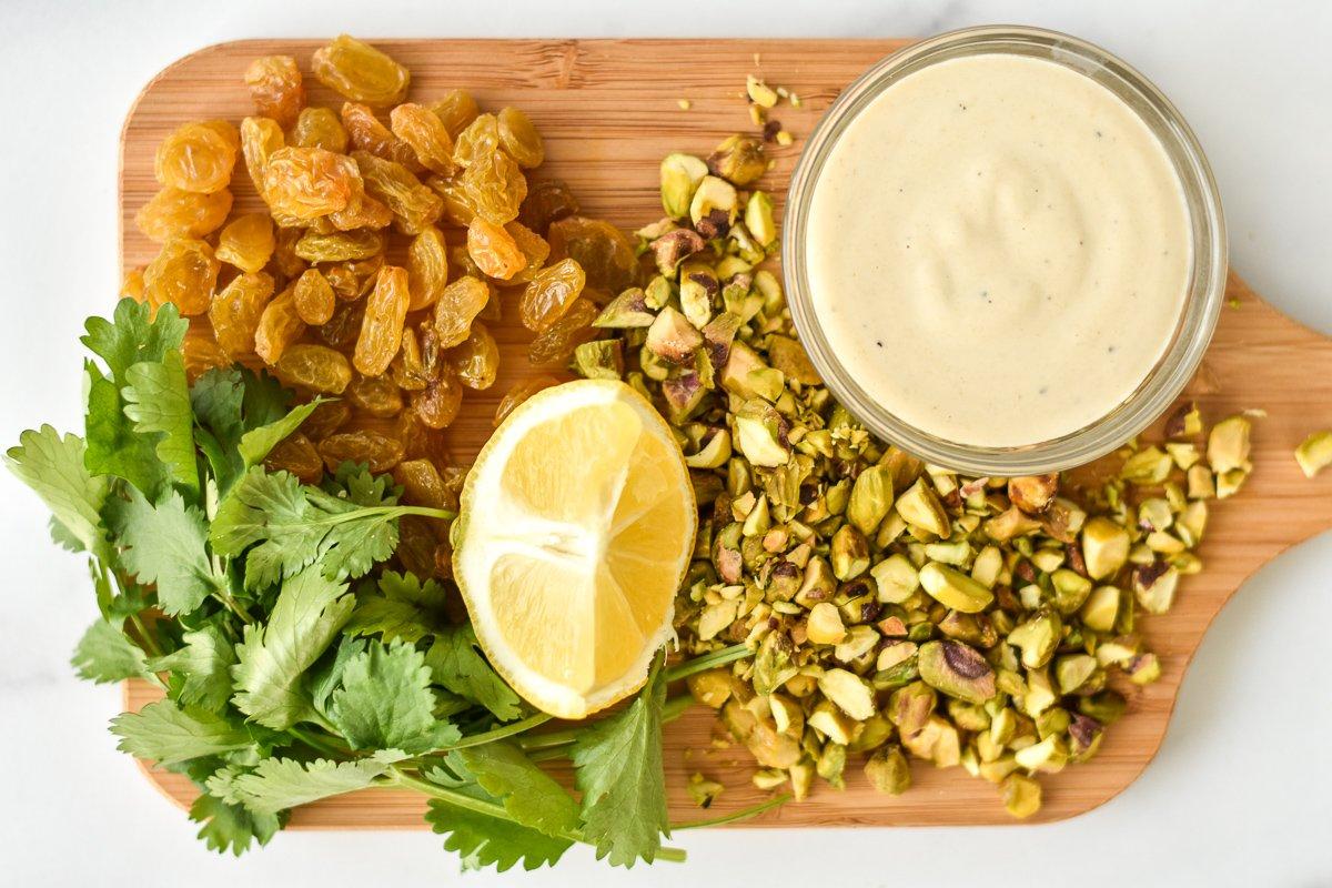 golden raisins, pistachios, cilantro, tahini and lemon wedge on a wood cutting board