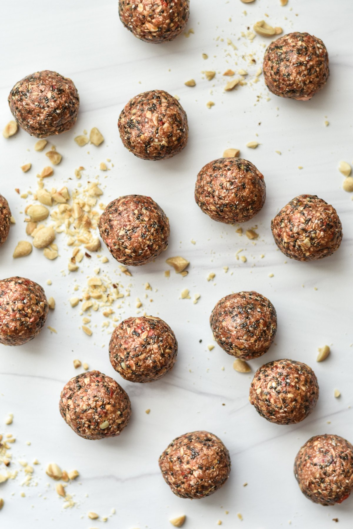 PB & J energy bites with crushed peanuts on a countertop