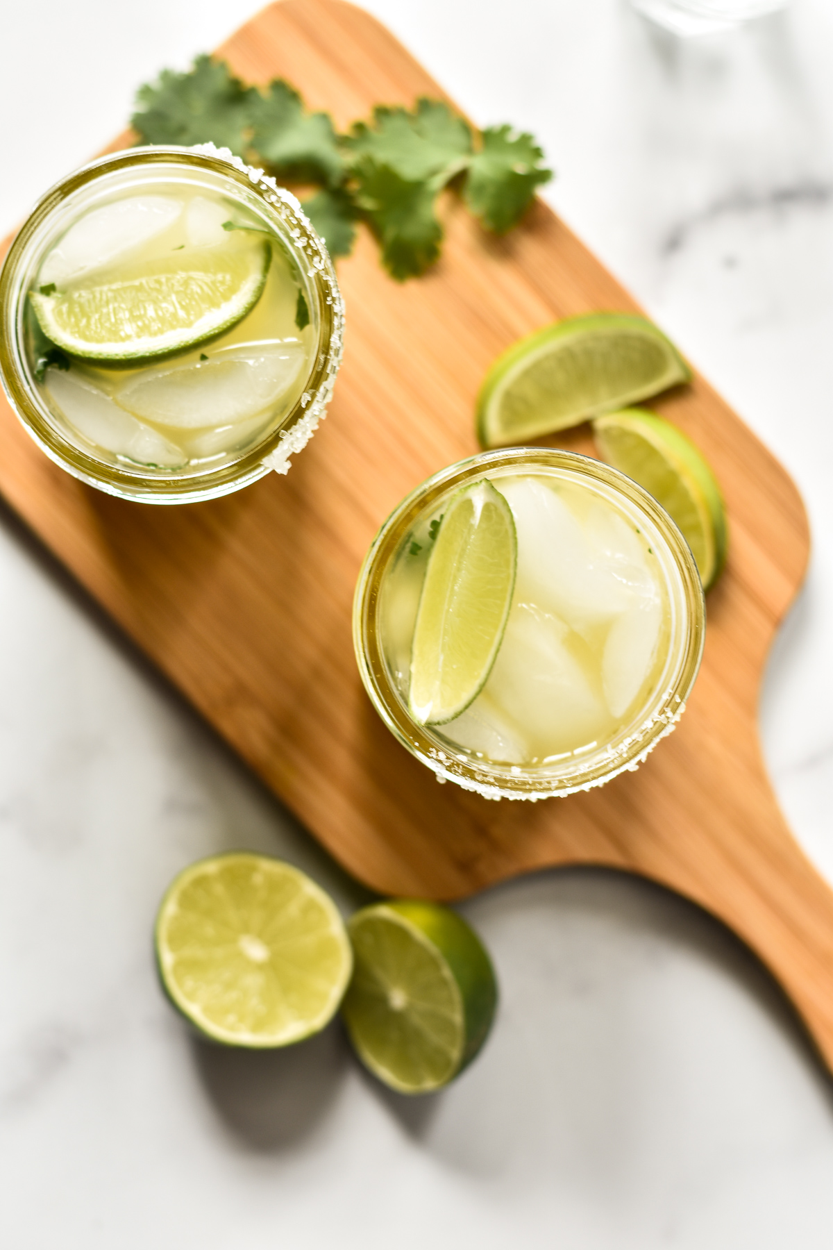two pineapple cilantro margaritas on a wooden cutting board with limes and cilantro