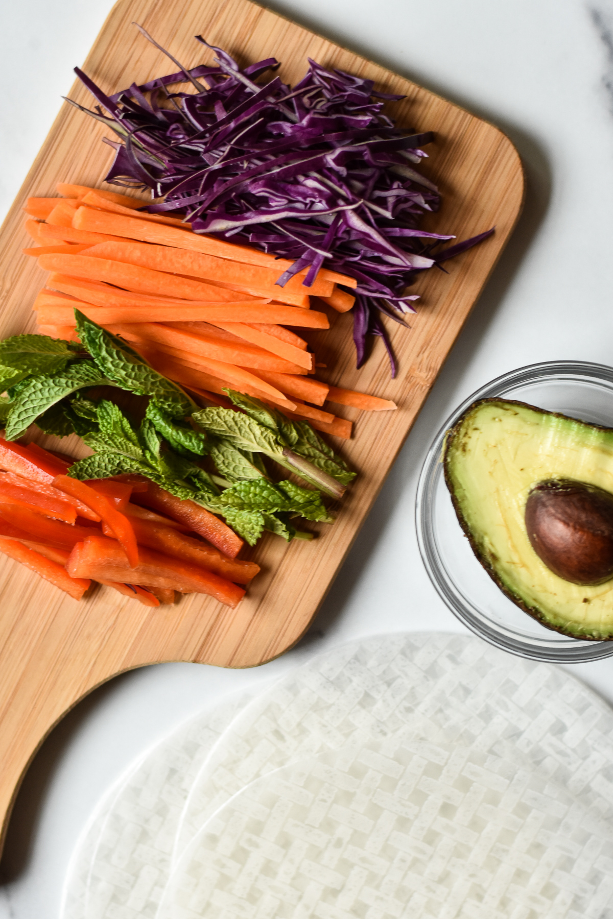 ingredients for summer rolls on a wooden cutting board