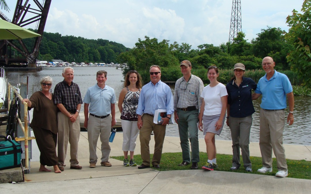 A group of 10 people stand with Rep. David Joyce on the banks of the Ashtabula River.