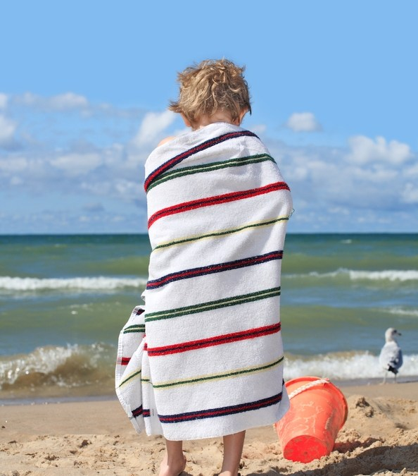 Child in a towel on a beach