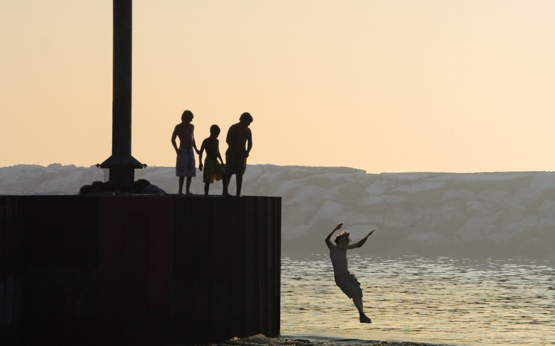 people jump off of a break wall in the Great Lakes