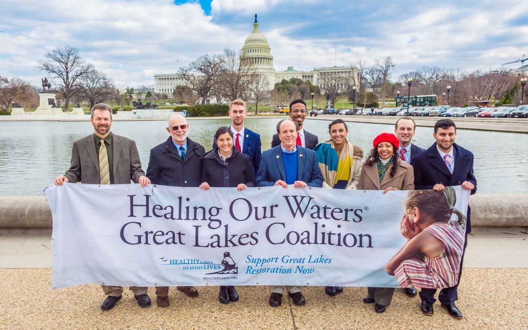A group of people behind a banner that say Healing Our Waters-Great Lakes Coalition on it with the capitol building in the background