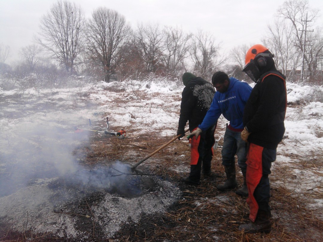 Crew members of the Calumet Conservation Corps start a burn to restore the ecosystem.