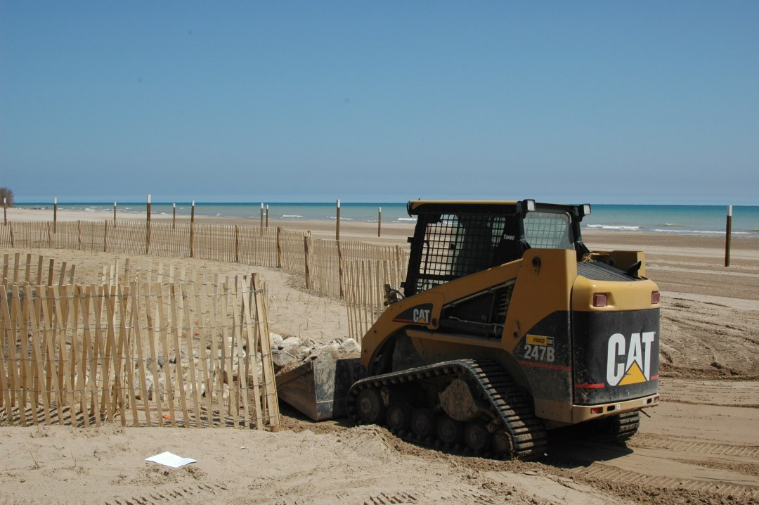 A front end loader moves sand on Bradford Beach