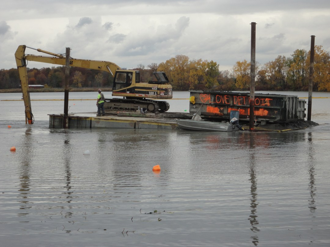 A barge working on restoring part of the Belle Isle lagoon