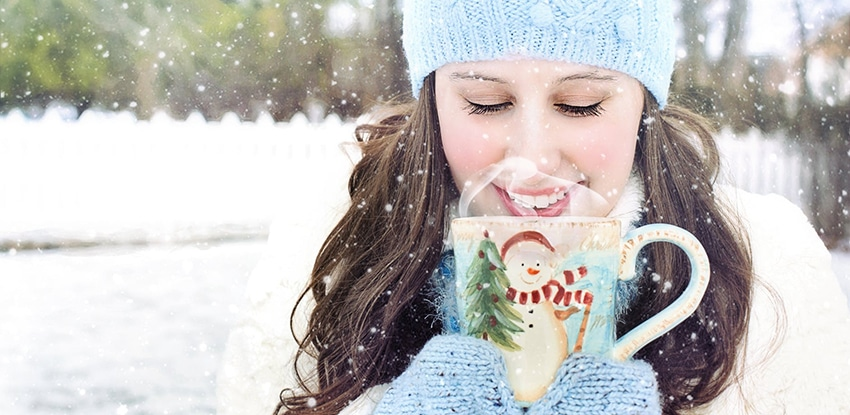 girl sipping hot chocolate in the snow