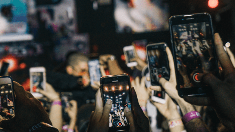 Lots of people at a concert trying to take a photo on their phones.