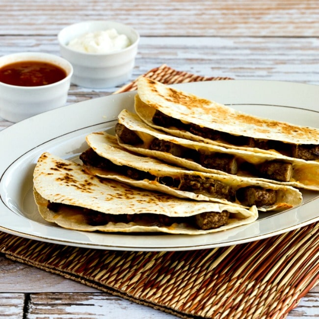 Sausage and Cheese Breakfast Quesadillas square thumbnail photo of tortillas on plate with salsa and sour cream on the side.