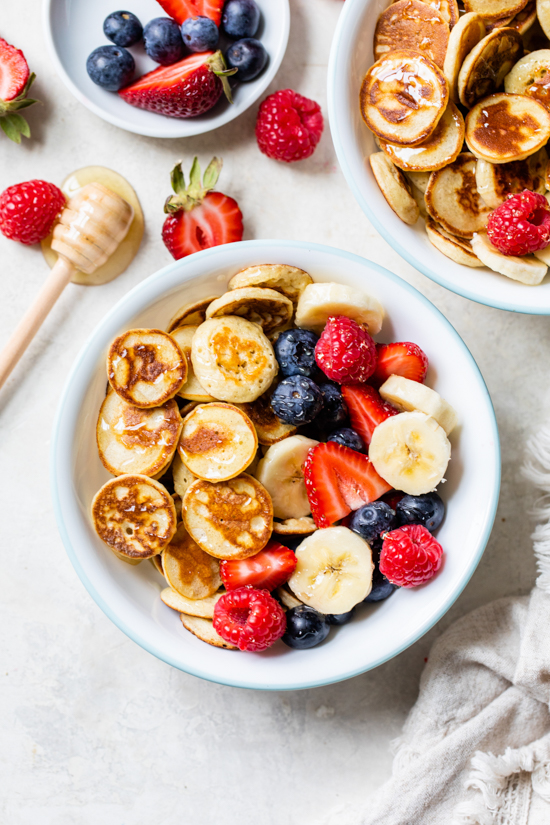 Mini Pancake Cereal is the latest Tiktok trend, so versatile you can serve them with anything you want! I made them healthier with my banana pancake recipe and topped them with tons of fresh fruit.