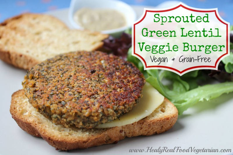 A close up of a Sprouted Lentil Burger on a bun with salad in the background