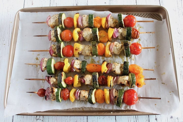 Overhead view of cooked chicken kabob skewers with vegetables and chicken on wooden skewers