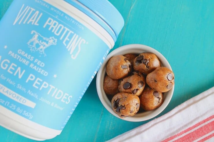 An overhead shot of energy balls in a ramekin and a tub of collagen peptides at the side