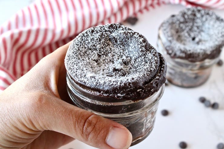 A hand holding a finished jar of chocolate keto mug cake over a white surface sprinkled with chocolate chips and a red and white striped dish towel